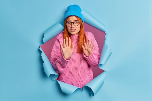 Una donna spaventata e nervosa in maglione e cappello lavorati a maglia fa il gesto di fermarsi e cerca di difendersi fissando qualcosa di spiacevole o spaventoso.