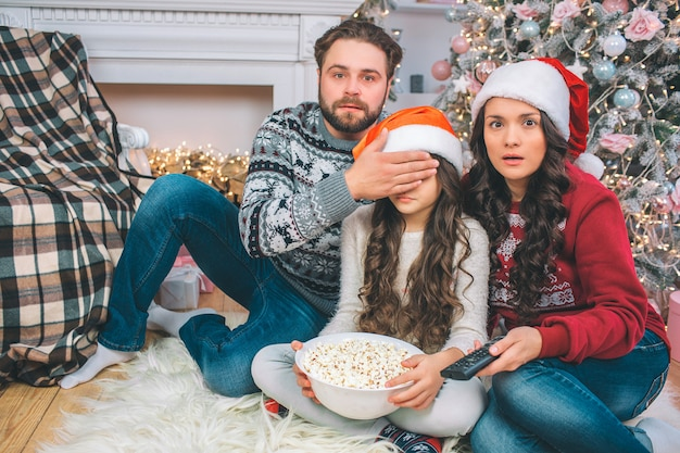 Scared parents look straight. father cover eyes of his daughter with hand. they watch together. girl holds bowl of popcorn. she sits between parents.