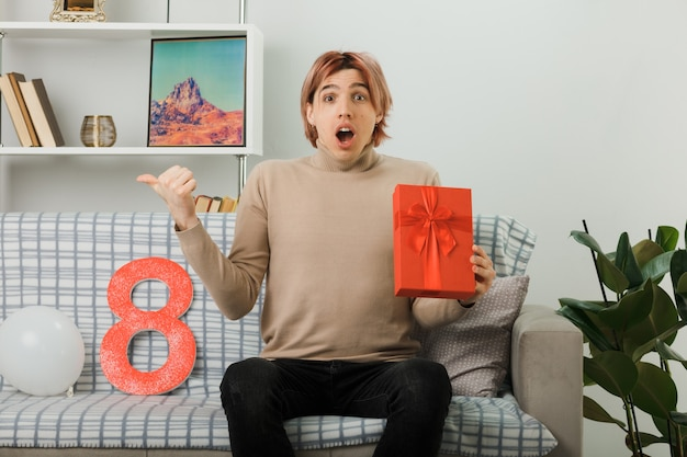 Scared points at side handsome guy on happy women day holding present sitting on sofa in living room