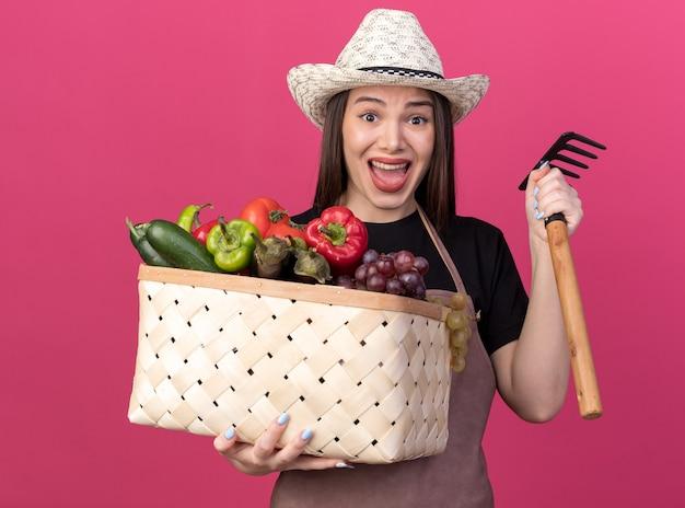 野菜のバスケットと熊手を保持しているガーデニング帽子をかぶっている怖いかなり白人女性の庭師