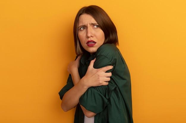 怖いかなり白人女性が腕を持って横向きに立ってオレンジ色の側面を見ています