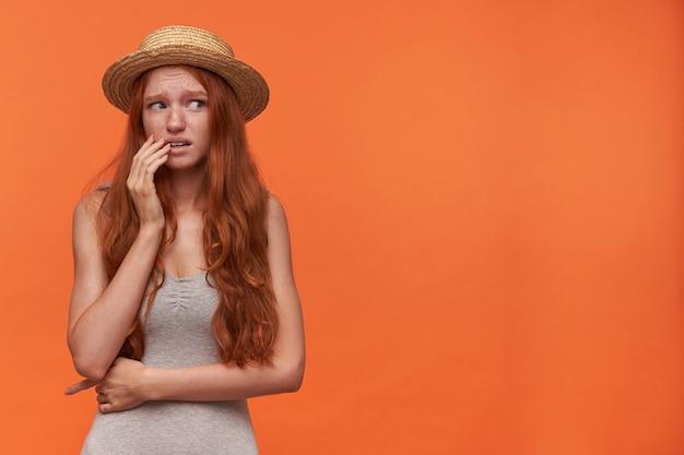 Spaventato piuttosto giovane foxy lond donna dai capelli in piedi su sfondi arancioni e tenendo la mano sul viso, guardando da parte con paura e accigliato, indossando abiti casual