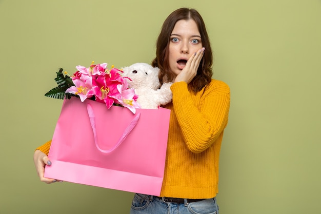 Scared putting hand on cheek beautiful young girl holding gift bag
