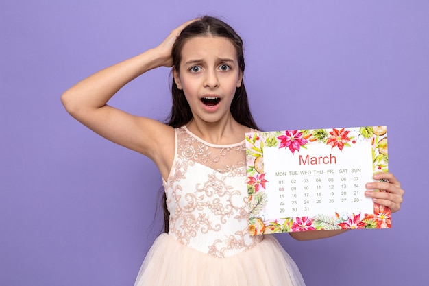 Scared putting hand on head beautiful little girl on happy woman's day holding calendar isolated on blue wall
