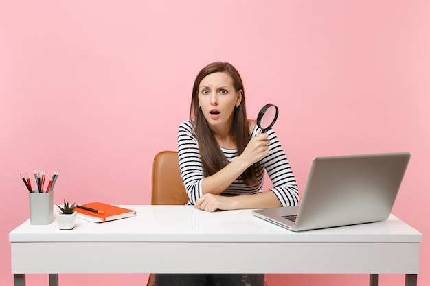 파스텔 핑크색 배경에 격리된 pc 노트북이 있는 흰색 책상에 앉아 돋보기를 들고 혼란스러워하는 겁에 질린 여성. 성취 비즈니스 경력 개념입니다. 공간을 복사합니다.