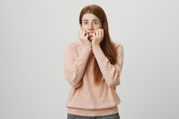 Scared redhead girl biting fingernails, looking frightened