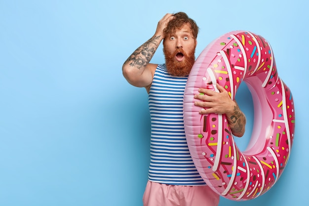 Scared redhead man recreats during summer holidays, holds pink swimring, shocked to forget necessary thing for rest, wears striped sailor vest and shorts keeps hand on head. omg concept