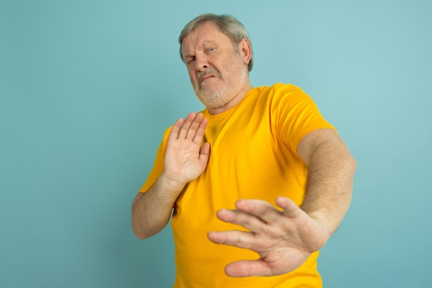Scared, rejecting. caucasian man portrait isolated on blue studio background. beautiful male model in yellow shirt posing.