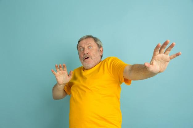 Испуганный, отвергающий. портрет кавказского человека, изолированные на синем фоне студии. красивая мужская модель в желтой рубашке позирует. понятие человеческих эмоций, выражения лица, продаж, рекламы. copyspace. Бесплатные Фотографии