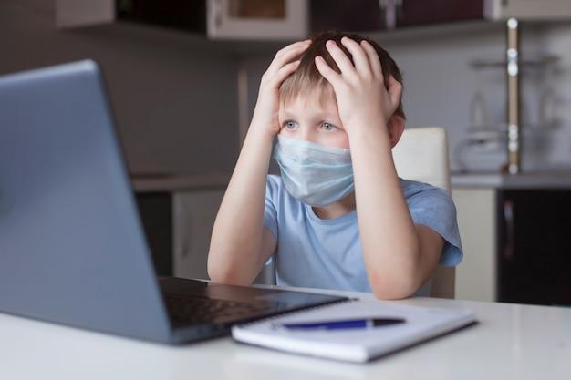 Испуганный школьник в медицинской маске дома изучает, делает школьную домашнюю работу