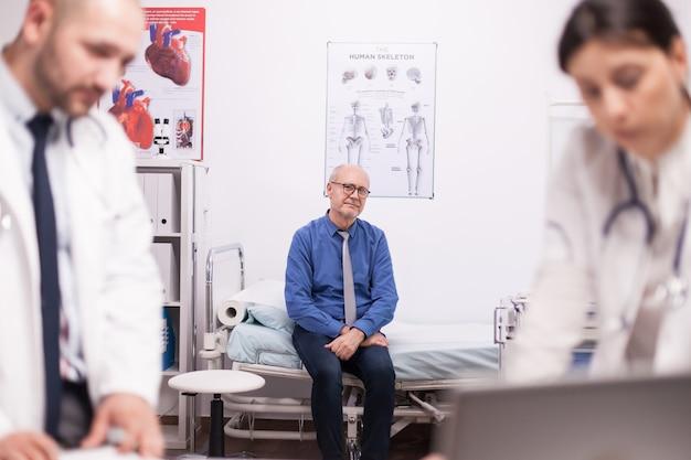 Испуганный старший пациент ждет диагноза от команды врачей в офисе больницы после осмотра. старик во время медицинского осмотра. медики в белом халате.