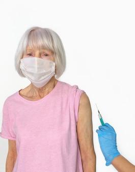 마스크를 쓴 겁에 질린 노인 여성과 예방 접종 중 주사기가 달린 의료용 장갑에 의사의 손