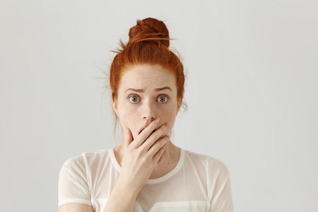 Ragazza graziosa dagli occhi di insetto spaventata e scioccata con i capelli arancioni che hanno sorpreso l'espressione facciale