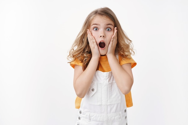 Scared and shocked caucasian blond little girl gasping, grab face amazed, stare camera astonished, drop jaw speechless observe shook event, react ambushed, frightened see spider, white wall