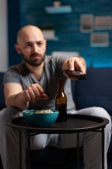 ポップコーンを食べるテレビでホラースリラー映画を見て怖いショックを受けた男