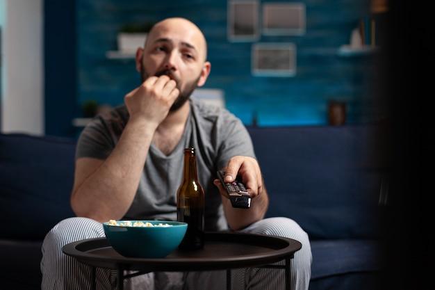 Scared shocked man looking at horror thriller movie at tv eating popcorn