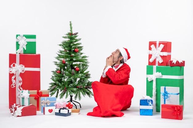 Paura scioccato giovane adulto vestito da babbo natale con doni e albero di natale decorato seduto per terra su sfondo bianco