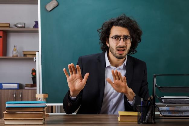Insegnante maschio che mostra il gesto di arresto con gli occhiali seduto al tavolo con gli strumenti della scuola in classe