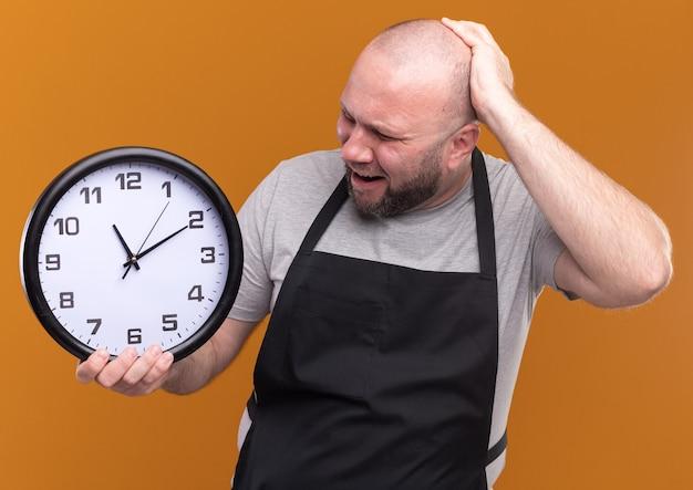 Barbiere maschio di mezza età slavo spaventato in uniforme che tiene e guardando l'orologio da parete mettendo la mano sulla testa isolata sulla parete arancione