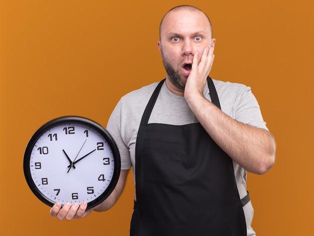 Spaventato barbiere maschio di mezza età slavo in uniforme che tiene l'orologio da parete mettendo la mano sulla guancia isolata sulla parete arancione