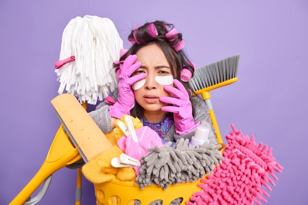 Scared stressed asian woman housekeeper applies collagen pads under eyes has frightened expression keeps hands on face makes hairstyle poses near laundry basket isolated over purple background.