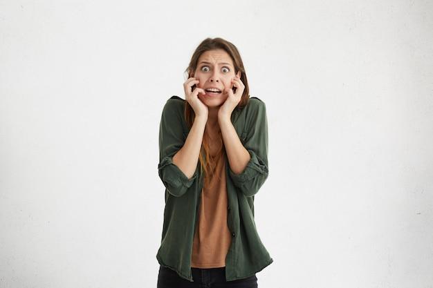 虫眼鏡の目で恐ろしい表情で彼女の顔に手を繋いでいる恐ろしいストレスの多い女性。