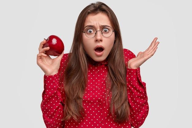 怖がっている愚かな黒髪の女性は驚きで見え、口を大きく開き、丸い眼鏡をかけ、ジューシーな果物を持っています