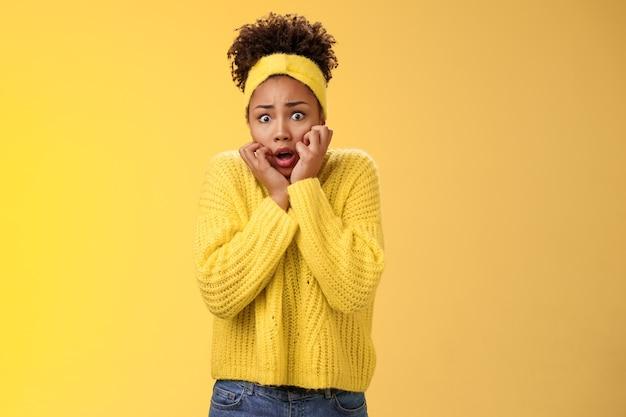 겁에 질린 겁에 질린 떨리는 불안한 소심한 아프리카계 미국인 여성이 두 눈을 크게 뜨고 헐떡이는 얼굴을 만지고 겁에 질린 표정 공포의 눈 겁에 질려 흔들리는 두려움, 서 있는 노란색 배경을 움직일 수 없습니다.