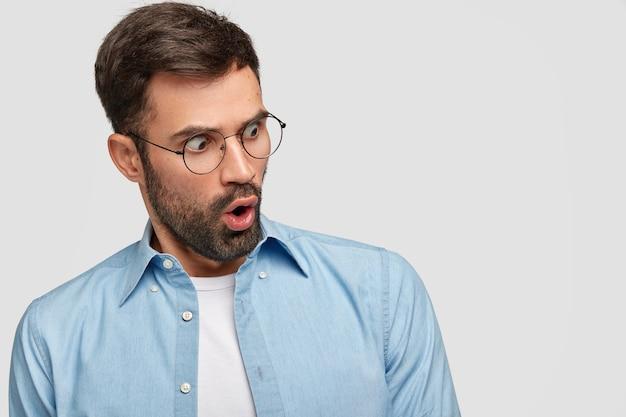 L'uomo barbuto spaventato e sorpreso fissa con espressione stupefatta, apre ampiamente la bocca, nota qualcosa di orribile, indossa gli occhiali