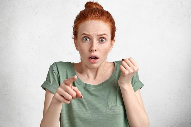 Испуганная, удивленная рыжая молодая женщина указывает на камеру с испуганным шокированным выражением лица, замечает что-то ужасающее, носит повседневную зеленую футболку, изолированную на белом студийном бетоне