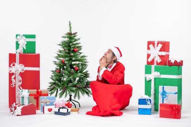 Spaventato sorpreso giovane adulto vestito da babbo natale con doni e albero di natale decorato seduto per terra su sfondo bianco
