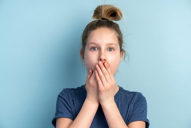 怖い10代の少女は彼女の手で彼女の口を覆います