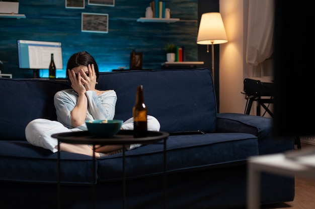 Scared terrified woman watching horror film on television eating popcorn