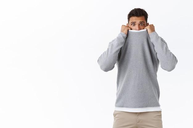 Испуганный, робкий и симпатичный молодой парень, который боится фильмов ужасов, натягивает свитер на лицо и хмурится с выгнутым печальным выражением лица, испуганный, стоя трясется от страха белая стена