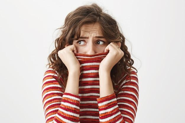 左を見て怖がって臆病な女性、震え、セーターの襟の中の顔を隠す