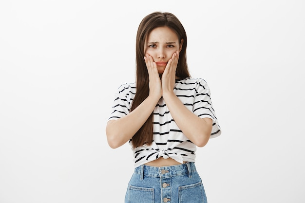 頬に手を繋いでいる怖がって臆病な若い女の子が心配している、心配している、または心配している