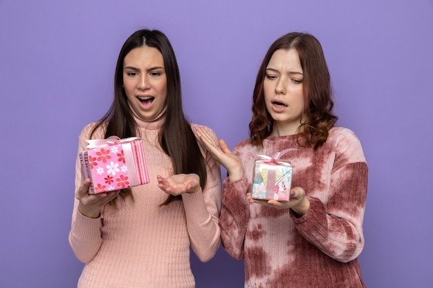 青い壁に隔離されたプレゼントを持って見て幸せな女性の日に2人の女の子を怖がらせた