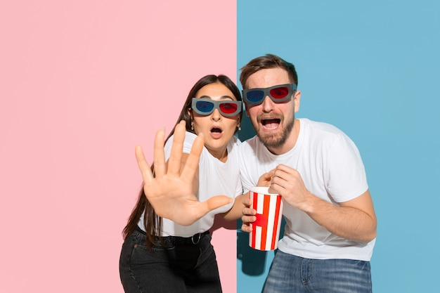 Scared watching 3d-cinema with popcorn. young and happy man and woman in casual clothes on pink, blue bicolored wall. concept of human emotions, facial expression, relations. beautiful couple.