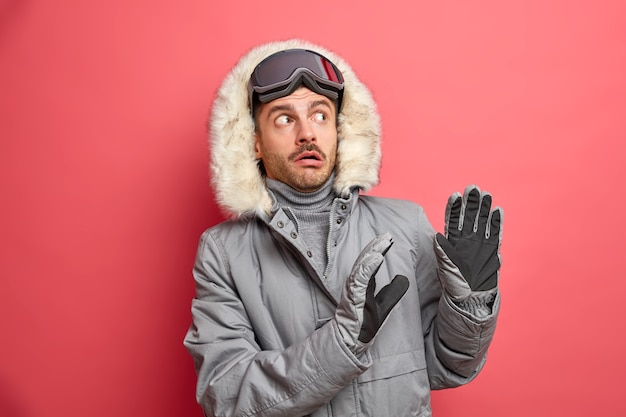Scared winter man makes defensive gesture afraids as something heavy going to fall on him wears grey jacket with fur hood and ski goggles.
