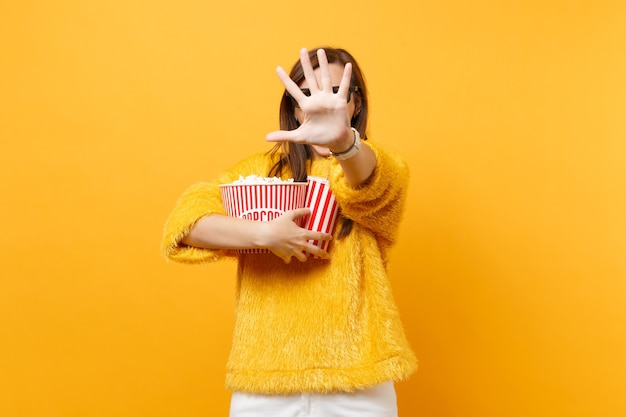 Scared woman in 3d imax glasses closing screen by hand, watching movie film, holding popcorn, plastic cup of cola or soda isolated on yellow background. people sincere emotions in cinema, lifestyle.