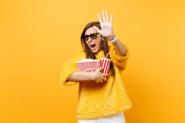 Scared woman in 3d imax glasses screaming trying to closing screen by palm watching movie film holding popcorn cup of cola isolated on yellow background. people sincere emotions in cinema, lifestyle.