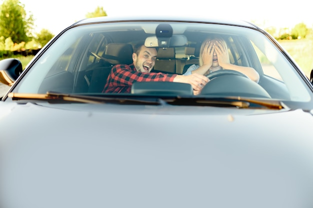 Испуганная женщина и инструктор в машине, вид спереди, автошкола. мужчина учит леди водить автомобиль. образование водительского удостоверения, авария