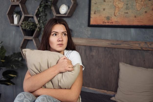 居間で枕を抱きしめて自宅で怖い女性