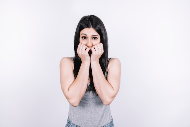 Scared woman biting nails