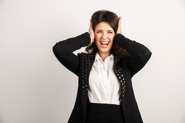 Donna spaventata che copre le orecchie su bianco
