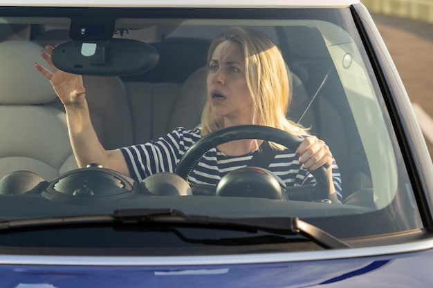 Scared woman driver look in back view mirror at small accident car crash on road or during parking