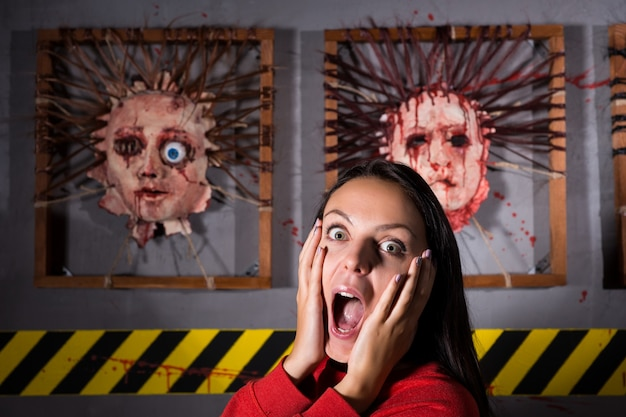 Scared woman in front of skinned faces for scary halloween theme terror crime scene