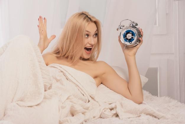Испуганная женщина, держащая будильник на кровати у себя дома