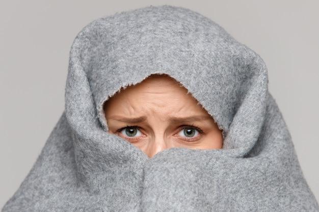 악몽 후 잠을 잘 수없는 격자 무늬 / 담요로 얼굴을 덮고 두려움에 무서워하는 여자