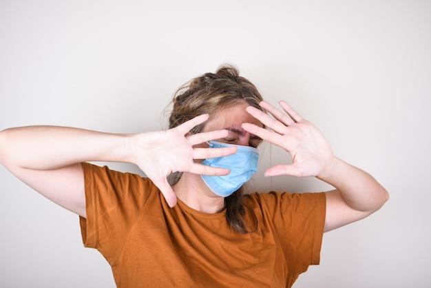 Испуганная женщина в медицинской маске закрывает лицо руками, изолированные